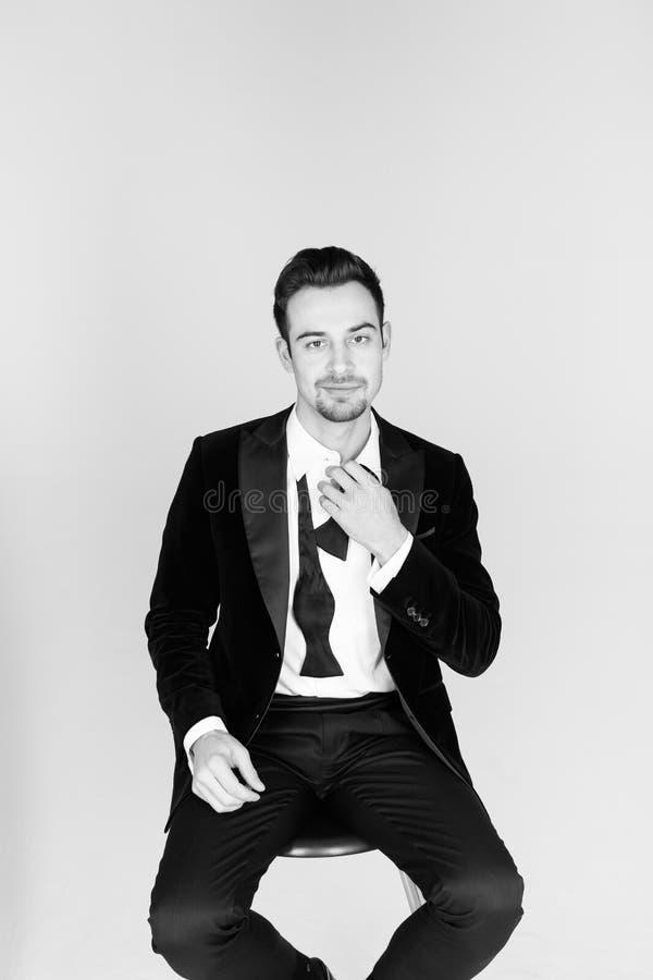 Ung stilig man, i en smoking, sammanträde och att se cameren royaltyfri foto