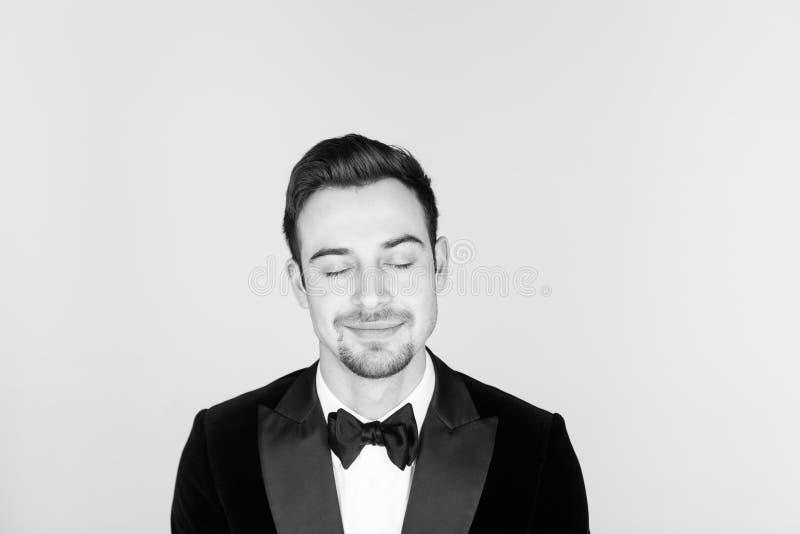 Ung stilig man i en smoking som ser kameran fotografering för bildbyråer