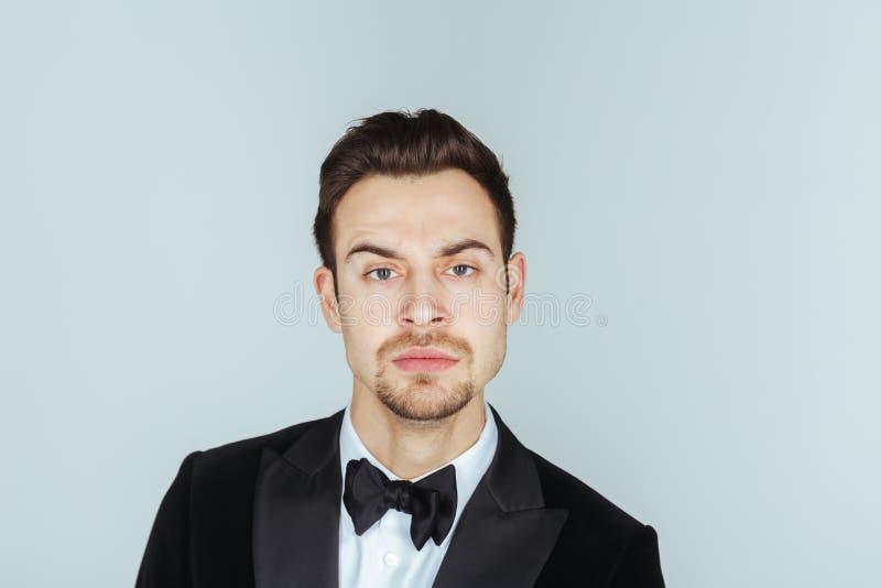 Ung stilig man i en smoking som ser setiously kameran royaltyfri foto