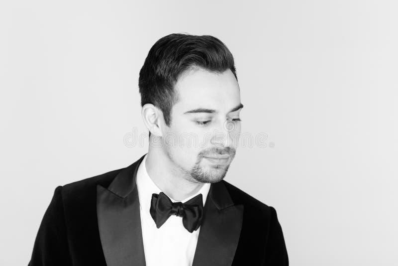 Ung stilig man i en smoking som ser till sidan fotografering för bildbyråer