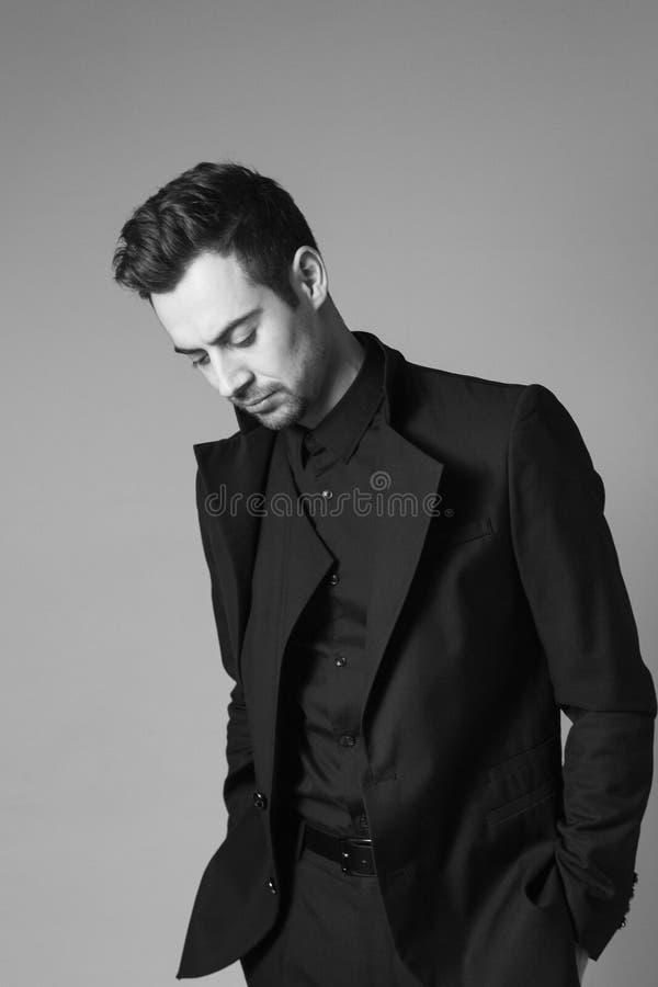 Ung stilig man i en svart dräkt, anseende som ner ser royaltyfri bild