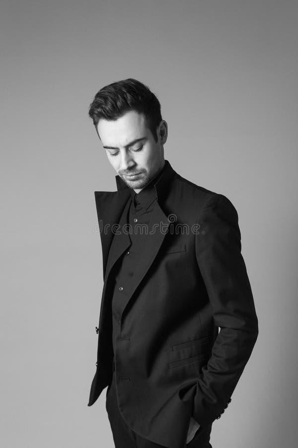 Ung stilig man i en svart dräkt, anseende som ner ser royaltyfria bilder