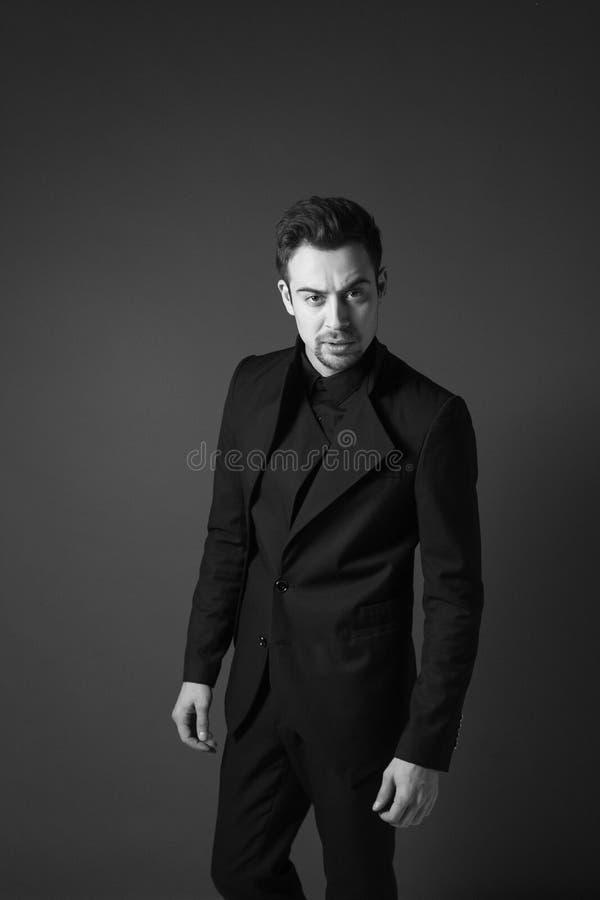 Ung stilig man i en svart dräkt, anseende som ser allvarligt royaltyfri bild
