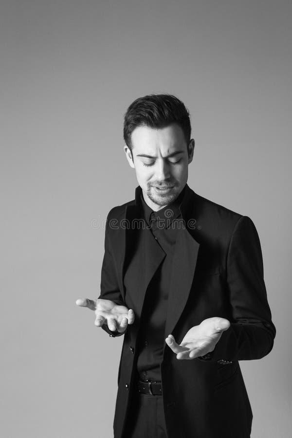 Ung stilig man i en svart dräkt, anseende som ser allvarligt royaltyfri foto