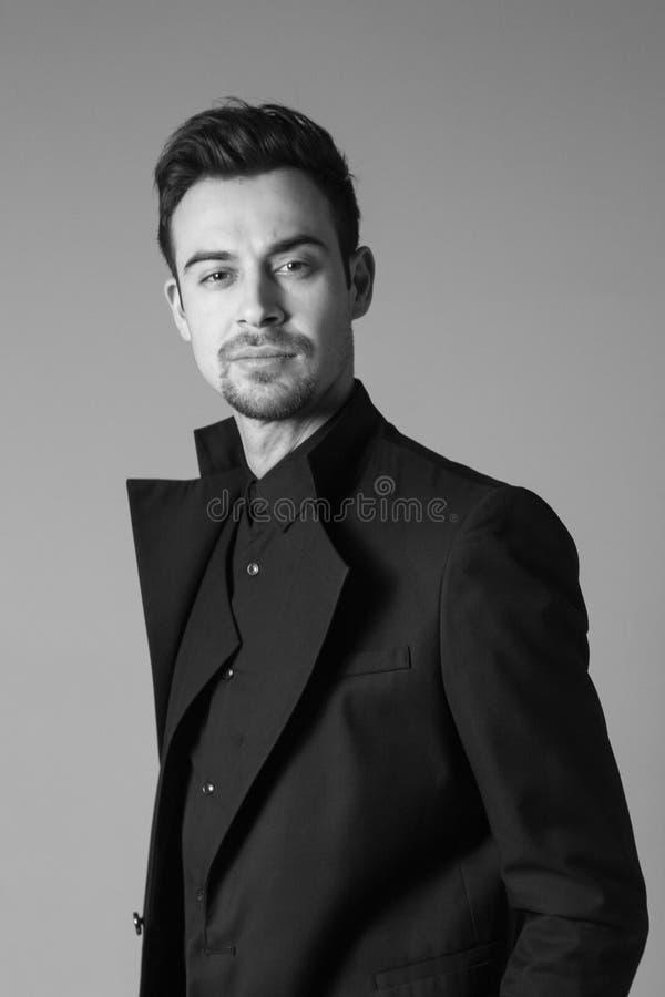 Ung stilig man i en svart dräkt, anseende som ser allvarligt royaltyfri fotografi