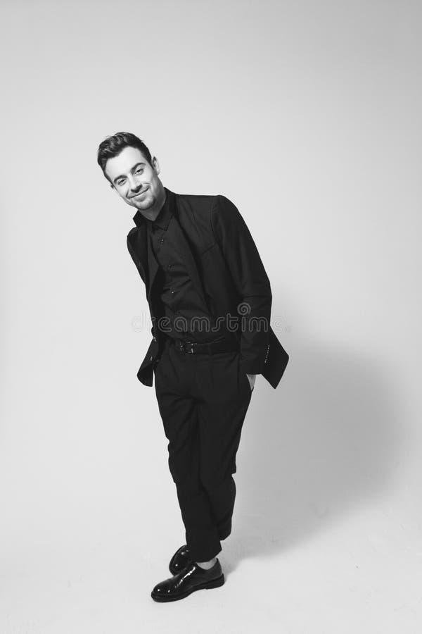 Ung stilig man i en svart dräkt som ler och ser cet royaltyfria foton