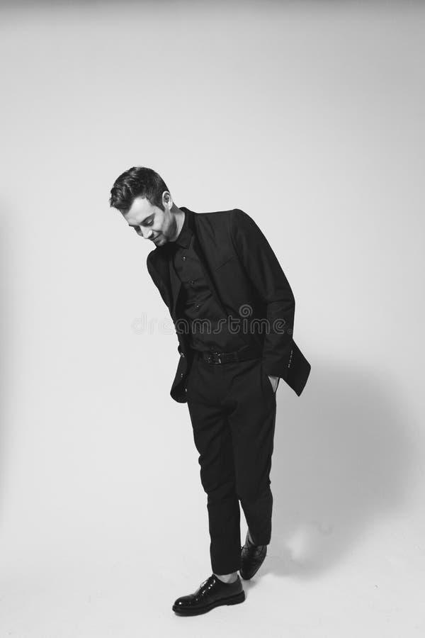 Ung stilig man i en svart dräkt som ner ler och ser royaltyfri foto
