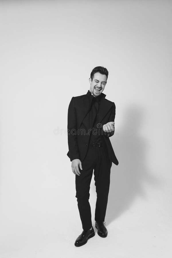 Ung stilig man i en svart dräkt som skrattar och ser royaltyfria foton