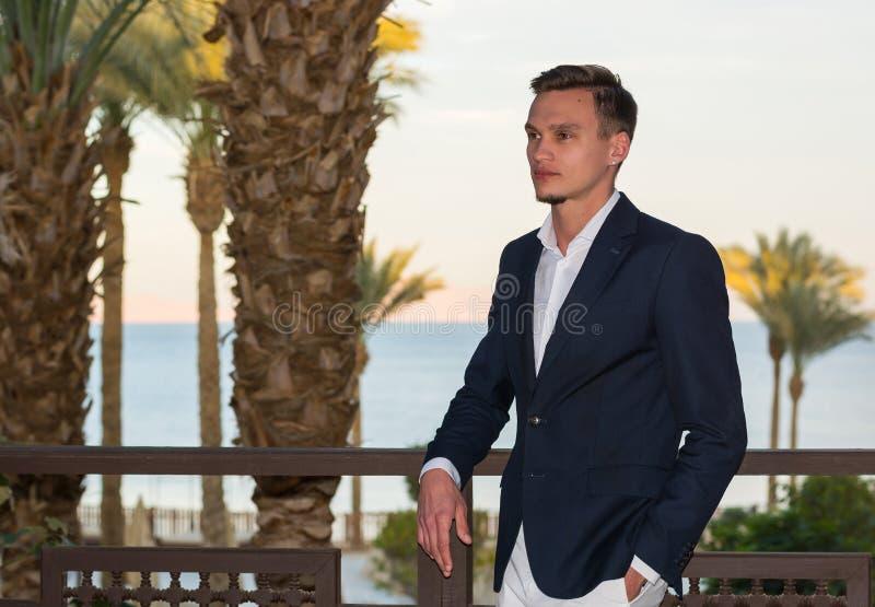Ung stilig man i en vit skjorta, en vit byxa och dräktställningar på balkongen på palmträd- och havsbakgrunden royaltyfria bilder
