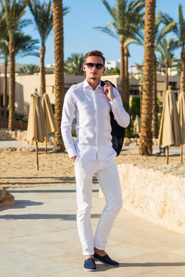 Ung stilig man i man i en vit skjorta och en vit byxa på palmträdbakgrunden på en strand arkivbild