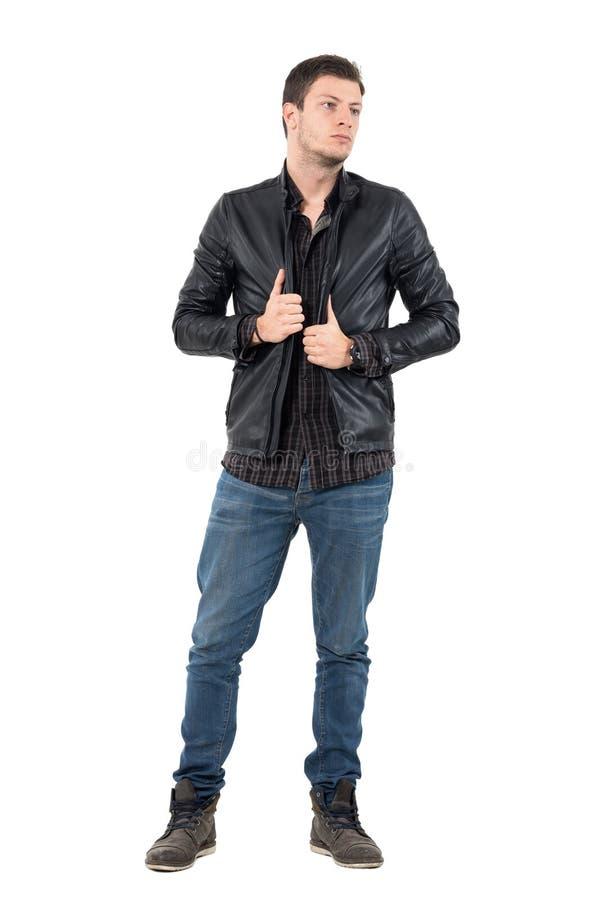 Ung stilig man i jeans som bär det svarta läderomslaget som bort ser arkivbild