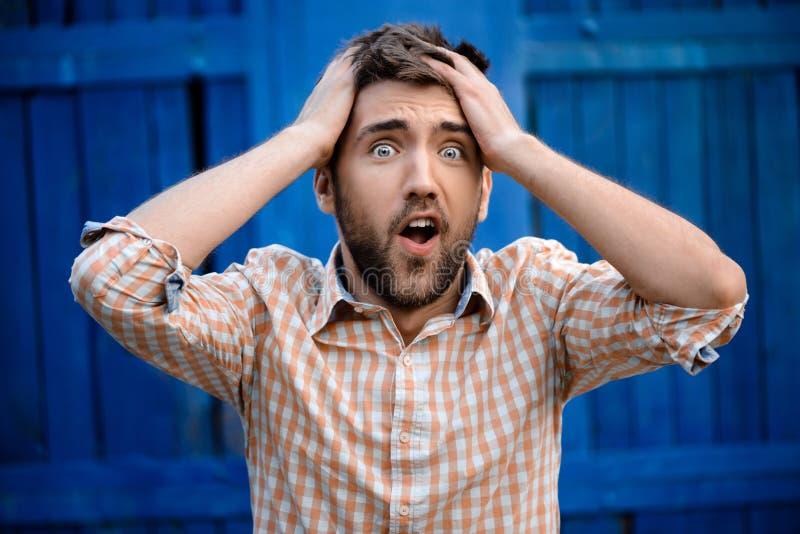 Ung stilig man i nervös over blå bakgrund för plädskjorta royaltyfria foton
