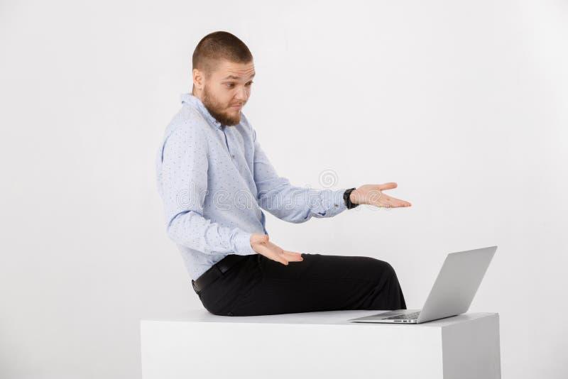 Ung stilig man i skjorta och band genom att använda bärbara datorn royaltyfria foton