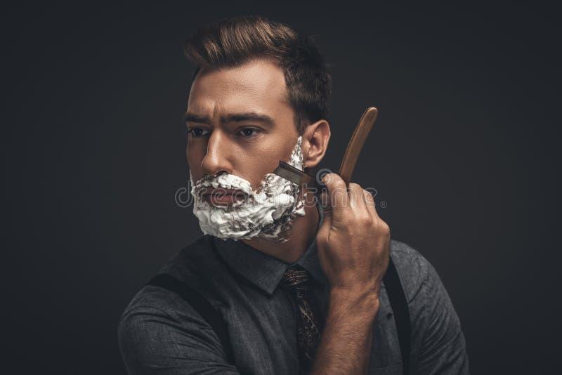 Ung stilig man med att raka kräm på hans framsida som ansar hans skägg arkivbilder