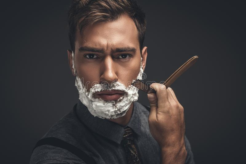 Ung stilig man med att raka kräm på hans framsida som ansar hans skägg med den raka rakkniven och att se royaltyfri fotografi