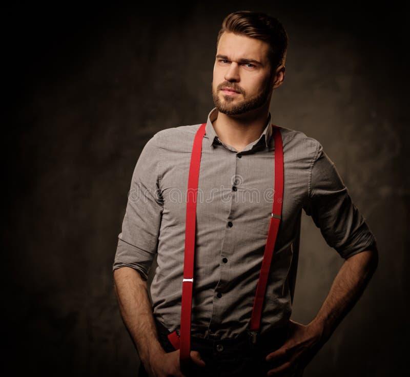 Ung stilig man med bärande hängslen för skägg och posera på mörk bakgrund fotografering för bildbyråer