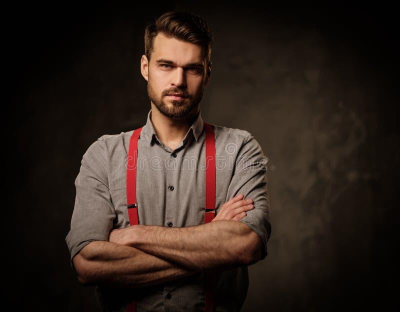Ung stilig man med bärande hängslen för skägg och posera på mörk bakgrund royaltyfri fotografi