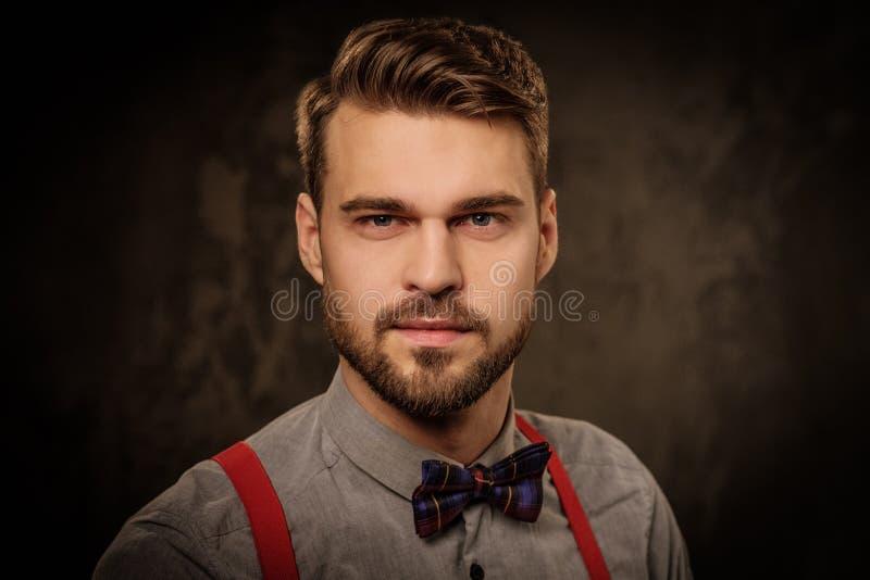 Ung stilig man med bärande hängslen för skägg och posera på mörk bakgrund arkivfoton
