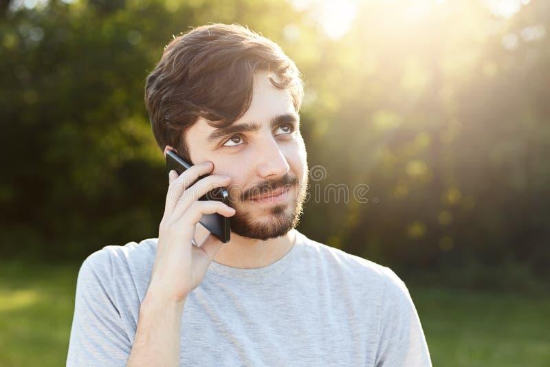 Ung stilig man med det tjocka skägget och mörka stora ögon som rymmer den smarta telefonen som ringer hans vän, medan stå på grön royaltyfri fotografi