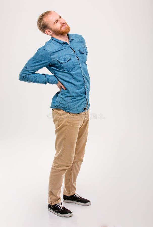 Ung stilig man med skägget som har en ryggvärk arkivbild