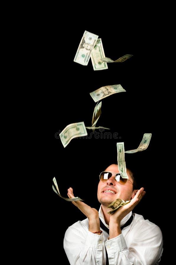 Ung stilig man och falla för pengar arkivfoton