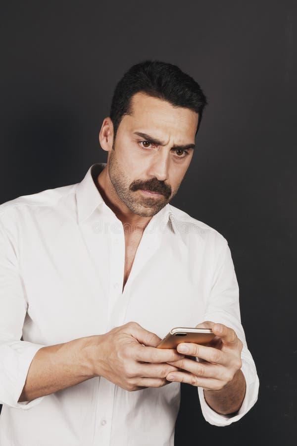 Ung stilig man som använder en mobiltelefon med en negativ inställning royaltyfri foto