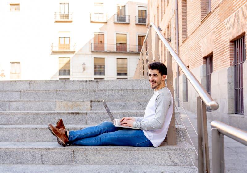 Ung stilig man som arbetar och studerar på bärbara datorn i en europé royaltyfri fotografi