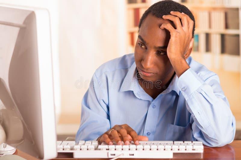 Ung stilig man som bär blått kontorsskjortasammanträde vid datorbenägenhet på skrivbordet, medan skriva och se oinspirerat arkivbild