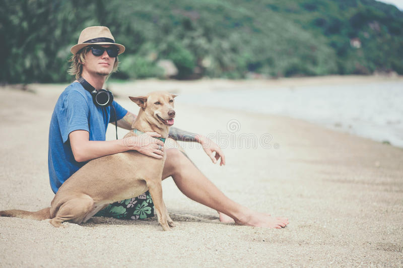 Ung stilig man som bär den blåa t-skjortan, hatten och solglasögon som sitter på stranden med hunden fotografering för bildbyråer