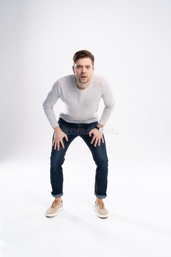 Ung stilig man som bär i tillfälligt rätt och chockar med överraskninguttryck, skräck och den upphetsade framsidan royaltyfri fotografi