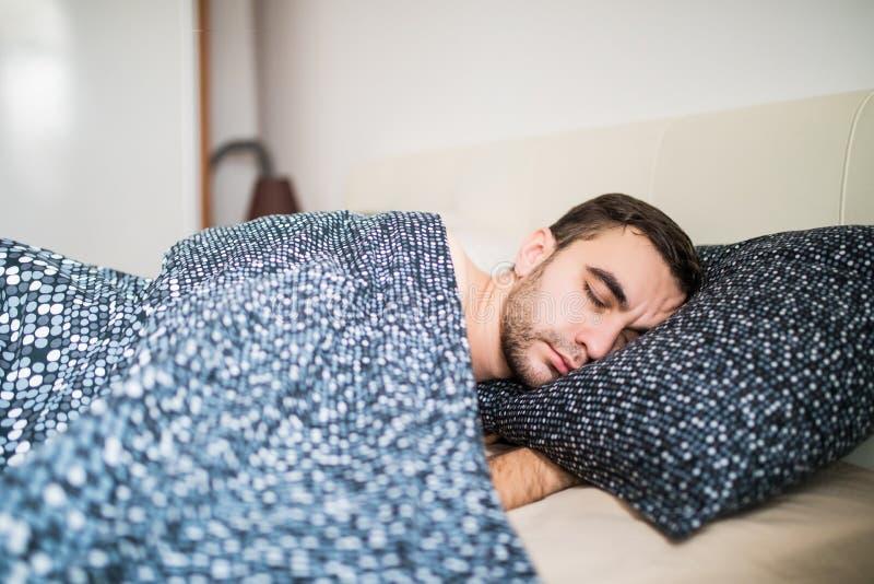 Ung stilig man som bekvämt hemma sover i säng royaltyfri bild