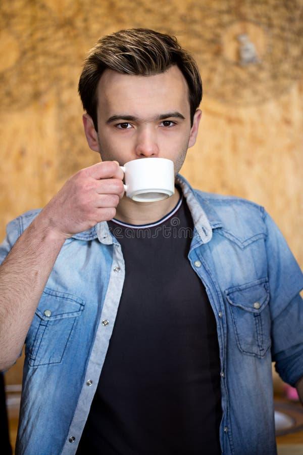Ung stilig man som dricker kaffe arkivbilder