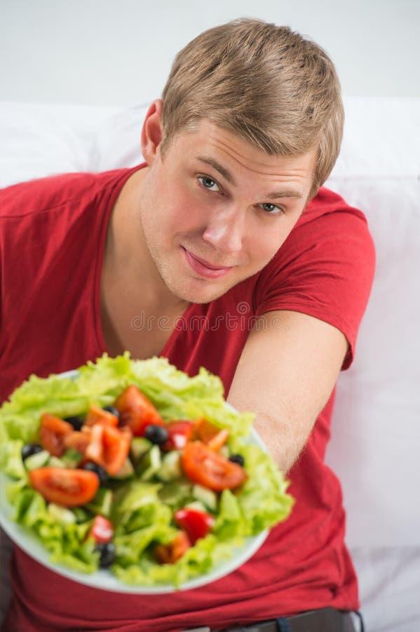 Ung stilig man som förbereder sig att äta ny sund sallad arkivbild