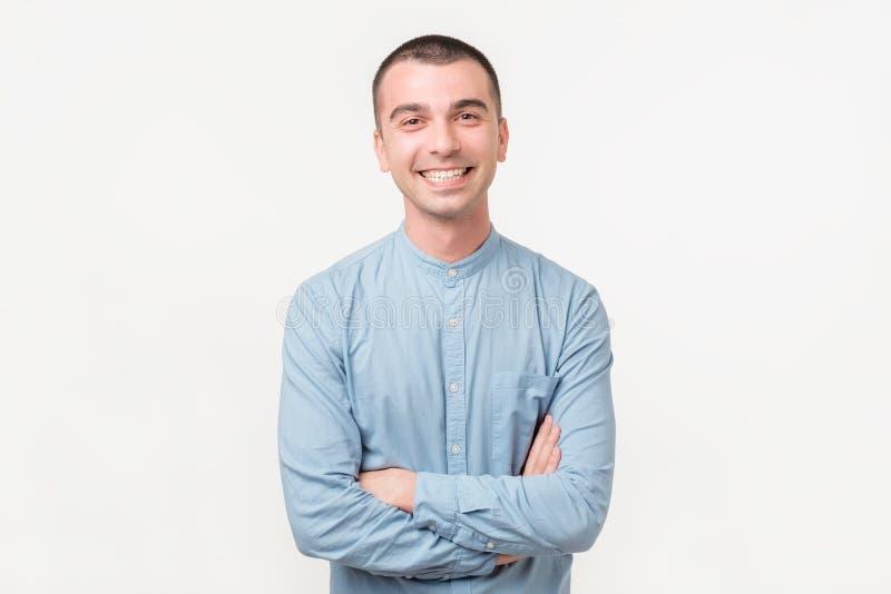 Ung stilig man som håller armar korsade och ler, medan stå mot vit bakgrund royaltyfria bilder
