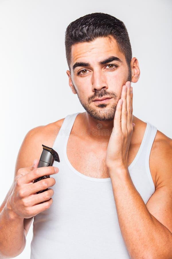 Ung stilig man som klipper hans skägg royaltyfri foto