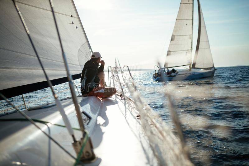 Ung stilig man som kopplar av på hans segelbåt arkivbild