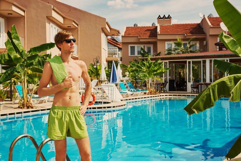 Ung stilig man som kopplar av vid simbass?ngen vila i semesterorthotell royaltyfri foto