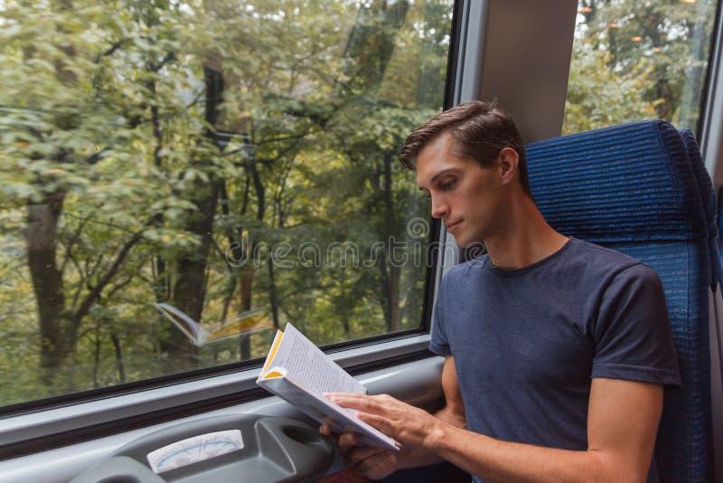 Ung stilig man som läser en bok, medan resa med drevet royaltyfria bilder