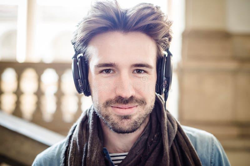 Ung stilig man som lyssnar till musik arkivfoto