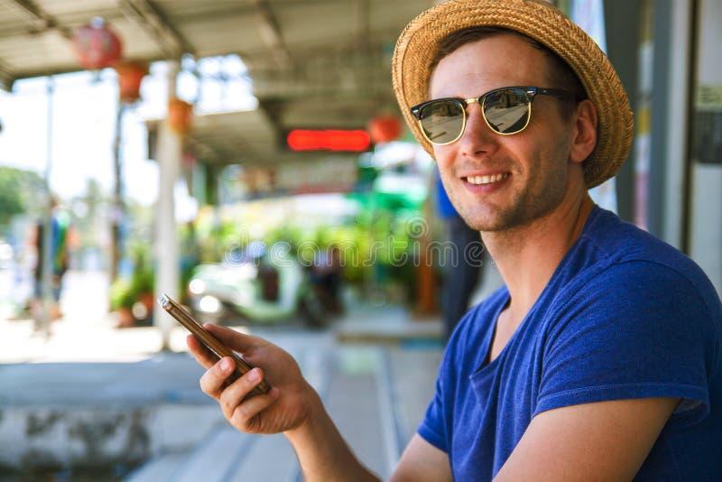 Ung stilig man som ner ser på mobiltelefonen med leende royaltyfri bild