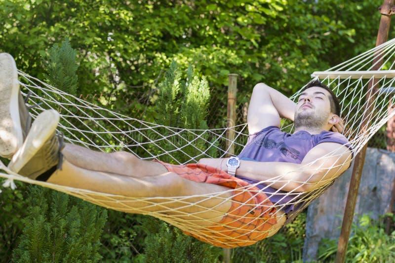 Ung stilig man som sover i hängmatta royaltyfri fotografi