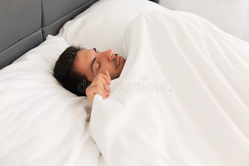 Ung stilig man som sover i hans säng arkivbild