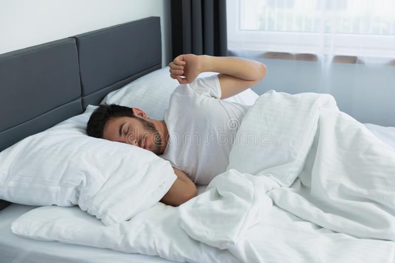 Ung stilig man som sover i hans säng arkivbilder