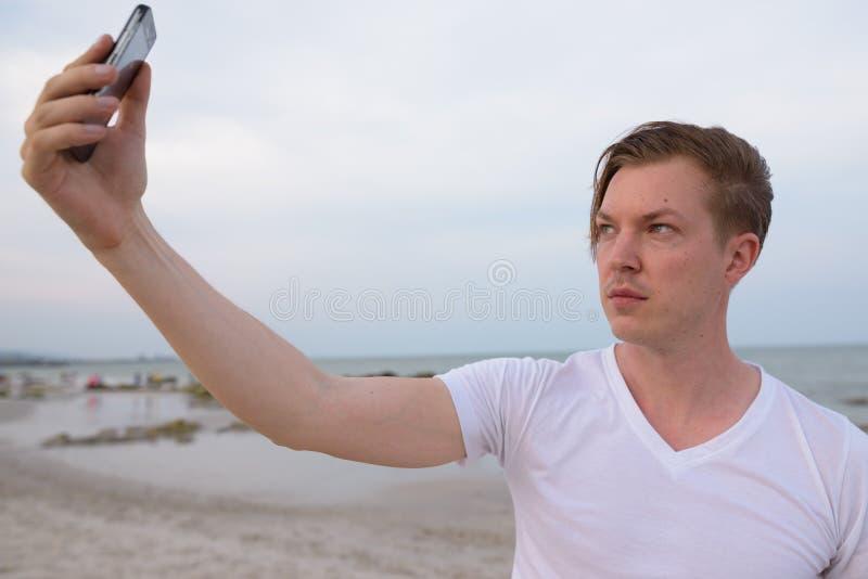 Ung stilig man som tar selfiebilden med mobiltelefonen på th arkivfoton