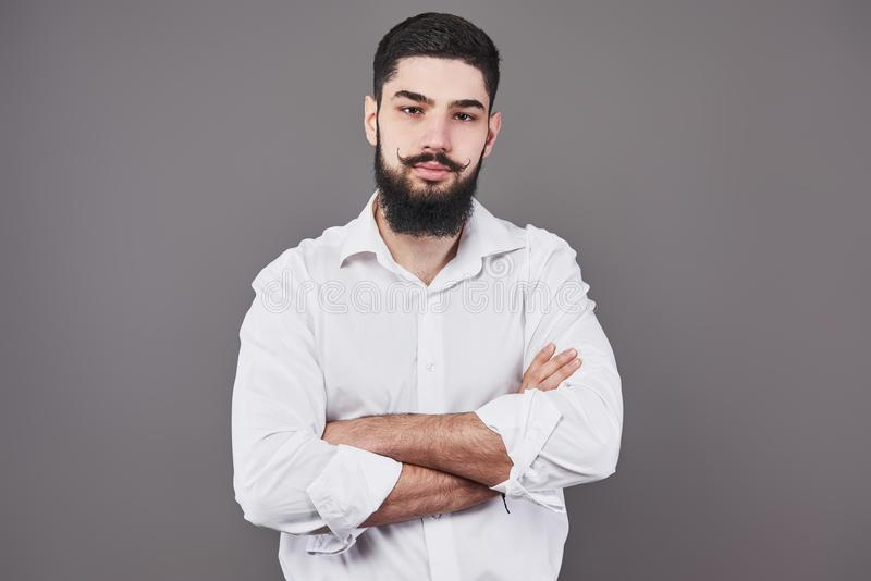 Ung stilig manbenägenhet mot den gråa väggen med korsade armar En allvarlig ung man med ett skägg ser kameran royaltyfria bilder