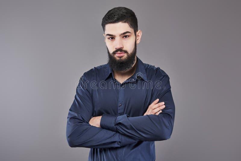 Ung stilig manbenägenhet mot den gråa väggen med korsade armar En allvarlig ung man med ett skägg ser kameran arkivfoto