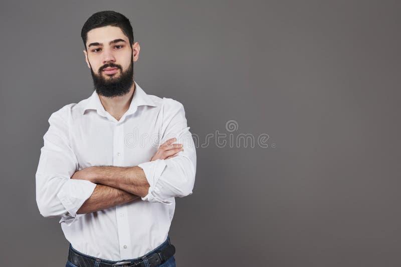 Ung stilig manbenägenhet mot den gråa väggen med korsade armar En allvarlig ung man med ett skägg ser kameran arkivbilder