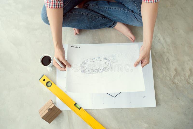 Ung stilig manlig asiatisk arkitekt som hemma arbetar på golvet fotografering för bildbyråer