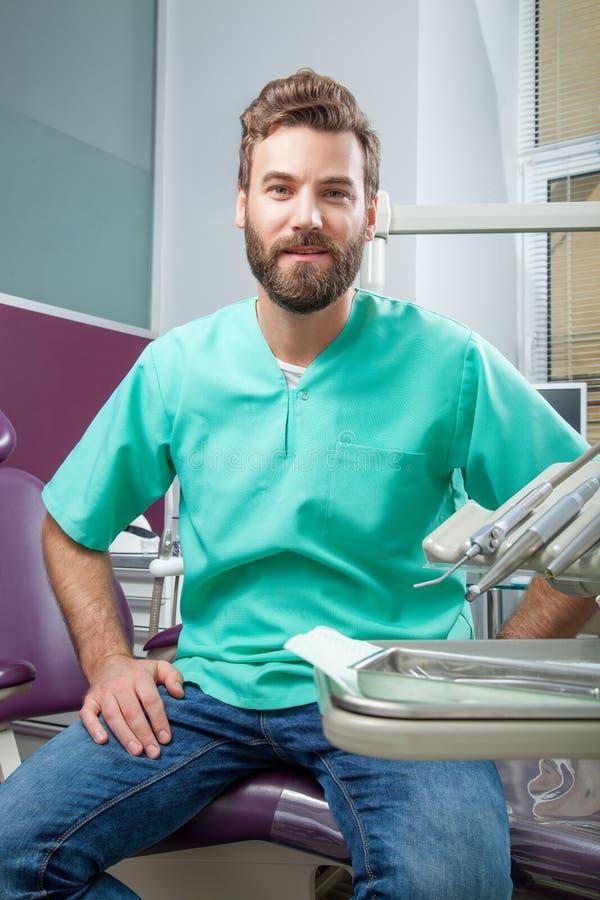 Ung stilig manlig doktor med skägget som ler med vita tänder royaltyfria bilder