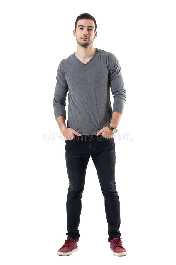 Ung stilig modemodell i grå skjorta med händer i fack som ser kameran royaltyfria bilder